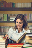 Beautiful woman happy among books Stock Photo