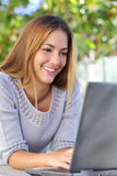 Beautiful woman happy browsing her laptop outdoor Royalty Free Stock Images