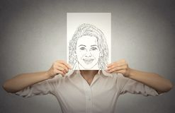 Beautiful woman with happy self portrait in front of her face, hiding true emotions Stock Photo