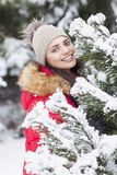 Beautiful woman is happy while is snowing in the park. Have fun during the winter season. World is more beautiful when is snowing around Stock Photos
