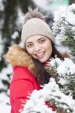 Beautiful woman is happy while is snowing in the park. Have fun during the winter season. World is more beautiful when is snowing around Stock Image