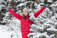 Beautiful woman is happy while is snowing in the park. Have fun during the winter season. World is more beautiful when is snowing around Stock Photo