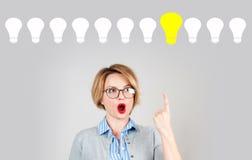 Beautiful woman has an idea.  Light bulbs Royalty Free Stock Photos