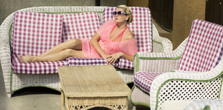 The beautiful woman has a rest on a sofa, in the open air Royalty Free Stock Photos