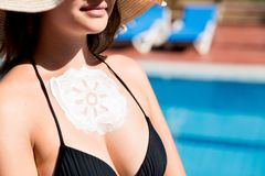 Beautiful woman has a sunscreen in sun shape on her breast by the pool. Sun Protection Factor in vacation, concept.  royalty free stock photo
