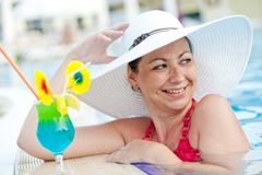 Beautiful woman in a hat and cocktail Royalty Free Stock Images
