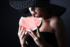 Beautiful woman with hat and eating watermelon on black background Royalty Free Stock Photo