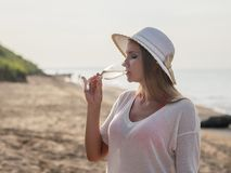 Beautiful woman in hat with glass of wine on the beach by the sea. Portrait of a woman with sparkling wine at the sea stock photo