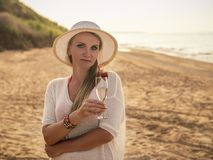 Beautiful woman in hat on the beach with a glass of wine and strawberry. Beautiful woman in hat with glass of wine on the beach by the sea. Portrait of a woman stock images