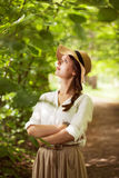 Beautiful woman in a hat among green foliage Royalty Free Stock Photos