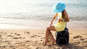 Beautiful woman in a hat with a jar of suntan cream in her hands sits on a suitcase against the sea during summer travel. Vacation. Beautiful happy woman with stock video