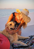 Beautiful woman in a hat with labrador nice dog on a yacht with sea landscape Royalty Free Stock Image
