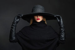 Beautiful woman in hat and leather gloves.halloween witch. Beautiful woman in hat and leather gloves. Retro fashion model girl.black hat with large brim royalty free stock photo