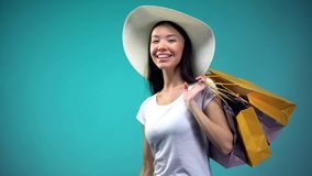 Beautiful woman in hat with paper bags looking at camera and smiling, shopping royalty free stock images