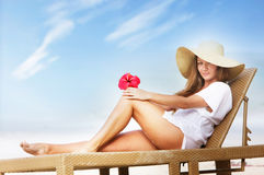 Beautiful woman in hat relaxing on beach Stock Photo