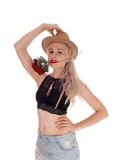 Beautiful woman with hat and rose in mouth. A lovely blond young woman standing in a black bra and jeans skirt with Stock Images