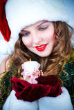 Beautiful woman in hat of Santa with a candle Royalty Free Stock Images