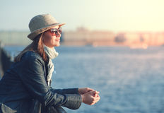Beautiful woman in hat and scarf enjoy sunlight in the city Royalty Free Stock Photography