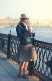 Beautiful woman in hat and scarf enjoy sunlight in the city Stock Images
