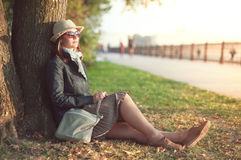 Beautiful woman in hat and scarf enjoy sunlight in the city Royalty Free Stock Images