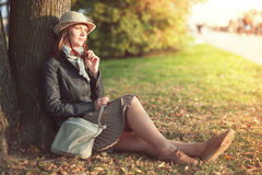 Beautiful woman in hat and scarf enjoy sunlight in the city Stock Photography