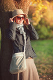 Beautiful woman in hat and scarf enjoy sunlight in the city Stock Photos
