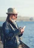 Beautiful woman in hat and scarf with mobile phone in the city Royalty Free Stock Images