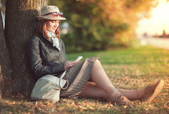Beautiful woman in hat and scarf with mobile phone outdoor Royalty Free Stock Images