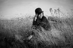 Beautiful woman with hat seated in field. Black and white portrait of beautiful dark haired woman wearing black and a hat seated in a field of grass in the early Stock Image