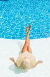 Beautiful woman in a hat sitting on the edge of the pool Royalty Free Stock Photo