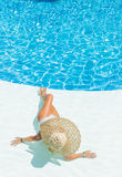 Beautiful woman in a hat sitting on the edge of the pool Stock Image