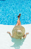 Beautiful woman in a hat sitting on the edge of the pool Stock Images