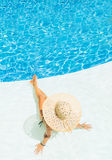 Beautiful woman in a hat sitting on the edge of the pool Royalty Free Stock Images