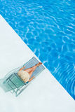 Beautiful woman in a hat sitting on the edge of the pool Royalty Free Stock Image
