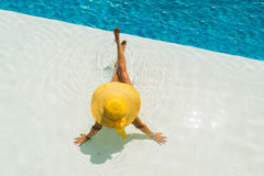 Beautiful woman in a hat sitting on the edge of the pool Stock Photo