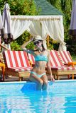 Beautiful Woman with hat sitting by the pool Royalty Free Stock Photography
