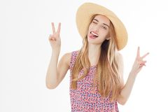 Beautiful woman with hat smiling on a background of white show victory signs and tongue.  royalty free stock images