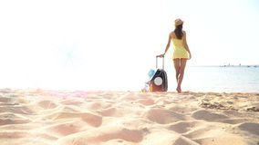 Beautiful woman in a hat stands on the beach with a suitcase and looks into the distance. 4k video.  stock footage