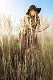Beautiful woman in hat in a tallgrass meadow at golden hour Stock Photography