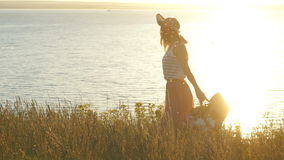 Beautiful woman in hat walking in the field and waves. The woman walks around the cliff along the river, slow motion stock video footage