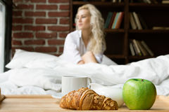 Beautiful Woman Having Breakfast in Bed. Breakfast in Bed on the Background of a Beautiful Young Woman Royalty Free Stock Photo