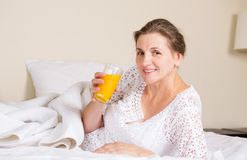 Beautiful woman having breakfast, in bed, bedroom of her house Stock Photo