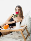Beautiful woman having breakfast in bed and smelling red rose Royalty Free Stock Image