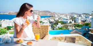 Beautiful woman having breakfast at outdoor cafe with amazing view. Girl enjoy her hot coffee early in the morning Royalty Free Stock Image