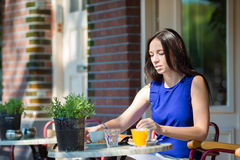 Beautiful woman having breakfast in outdoor cafe at european city Stock Images