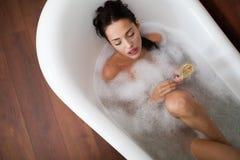 Beautiful woman having a bubble bath. Beautiful woman enjoying bubble bath Stock Photo