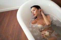 Beautiful woman having a bubble bath. Beautiful woman enjoying bubble bath Royalty Free Stock Photos