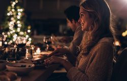 Beautiful woman having christmas dinner with family. Beautiful young women sitting with family and having christmas dinner. Family celebrating christmas together Stock Photos