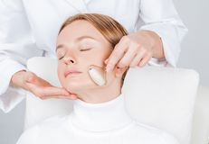 Beautiful woman having face treatment, cosmetologist massaging chin with jade rollers stock images