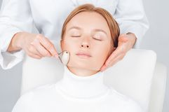 Beautiful woman having face treatment, cosmetologist massaging chin with jade rollers stock photography